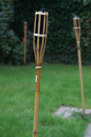 torches: Tall garden torches, on green grass Stock Photo