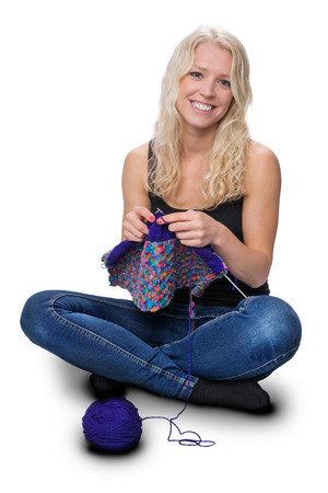 red jeans: A young pretty girl with blond hair, knitting, isolated on white background.