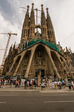 sagrada: The Sagrada Familia cathedral under construction and tourists Editorial