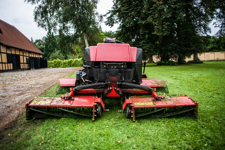 machinery space: Red lawn mower tractor machine and green grass
