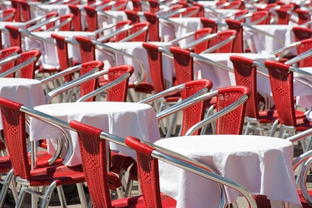 rows of empty red chairs and tables photo