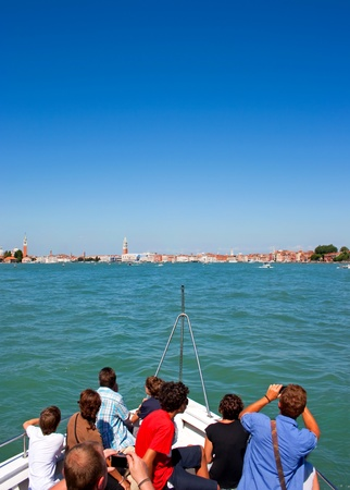 shafts: group of tourists on a boat converging to venice, italy.