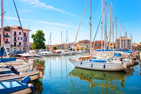 azure coast: Beautiful scene of boats lying in the harbor of Grado, Italy at Adriatic Sea   Stock Photo