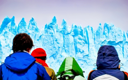 A group of tourists looking at gigantic icebergs