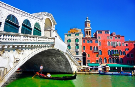 Famous Ponte di Rialto with traditional Gondola under the bridge in Venice, Italy