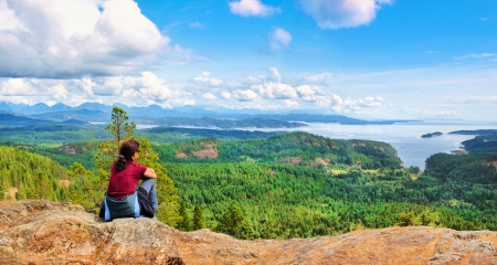 hardy: Woman sitting on a rock and enjoying the beautiful view on Vancouver Island, British Columbia, Canada Stock Photo