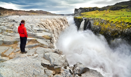 lowlands: Woman standing near famous Dettifoss waterfall in Vatnajokull National Park, Northeast Iceland Stock Photo