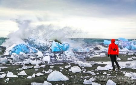 jokulsarlon: Woman watching waves crash against icebergs at Jokulsarlon glacial lagoon near Vatnajokull National Park, southeast Iceland Stock Photo