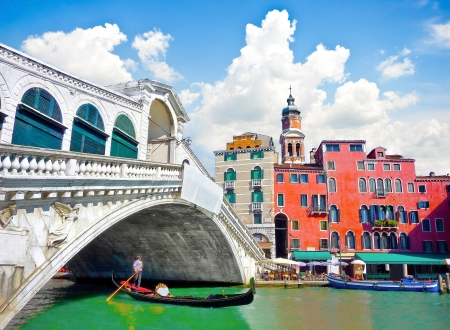 Famous Ponte di Rialto with traditional Gondola under the bridge in Venice, Italy photo