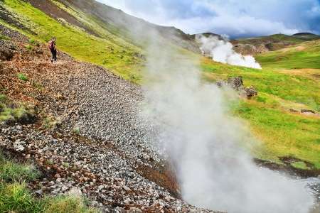 crater highlands: Woman hiking on trail in beautiful geothermal landscape along geysers in Hveravellir, Iceland