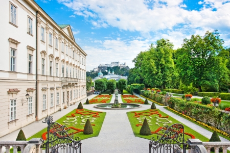 Beautiful view of famous Mirabell Gardens with Mirabell Palace and the old historic Fortress Hohensalzburg in the background in Salzburg, Austria