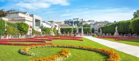 amadeus: Panoramic view of famous Mirabell Gardens with the old historic Fortress Hohensalzburg in the background in Salzburg, Austria