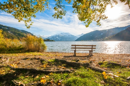 salzburg: Beautiful autumn scene with park bench and mountain lake in the Alps, Zell am See, Salzburger Land, Austria