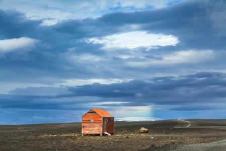 Panoramic view of barren landscape with old red snowstorm shelter at Kjolur highland road, Iceland Stok Fotoğraf