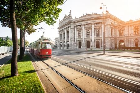歴史的なブルク劇場帝国裁判所の劇場と伝統的な赤い電気路面電車日没時オーストリアのウィーンで有名なウィナー リングシュトラーセの美しい景 報道画像