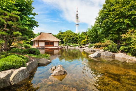 Beautiful view of Japanese Garden in Planten um Blomen park with famous Heinrich-Hertz-Turm radio telecommunication tower in the background, Hamburg, Germany
