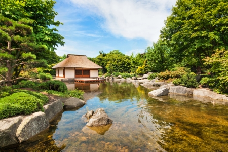 Beautiful view of traditional Japanese Garden with tea house and pond