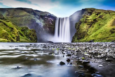 La exposición a largo de la famosa cascada de Skogafoss en Islandia en la oscuridad