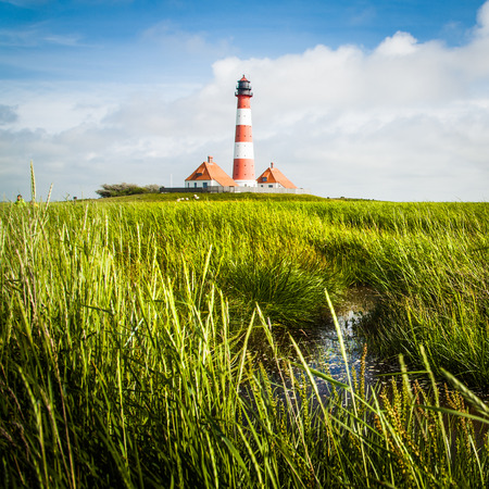 westerheversand lighthouse: Beautiful view of landscape with small pond and lighthouse in the background at North Sea in Nordfriesland, Schleswig-Holstein, Germany Stock Photo