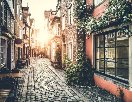 personas en la calle: La ciudad antigua de Europa al atardecer con efecto retro estilo vintage filtro Editorial