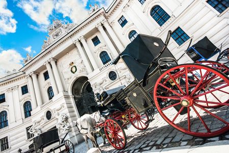 hofburg: Wide-angle view of famous Hofburg Palace with traditional horse-drawn Fiaker carriages on a sunny day in Vienna, Austria