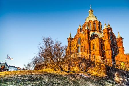 Beautiful view of famous Eastern Orthodox Uspenski Cathedral  Uspenskin katedraali  on a hill in the golden evening light on Katajanokka peninsula, Helsinki, Finland photo
