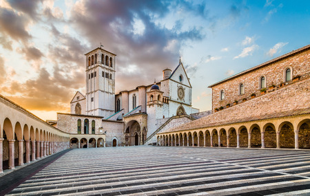 Famous Basilica of St. Francis of Assisi (Basilica Papale di San Francesco) with Lower Plaza at sunset in Assisi, Umbria, Italy Stock Photo