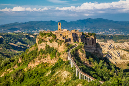Ancient town of Civita di Bagnoregio with Tiber river valley in golden evening light, Lazio, Italy
