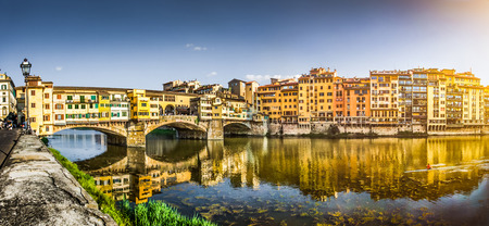 Panoramic view of famous Ponte Vecchio with river Arno at sunset in Florence, Tuscany, Italy photo