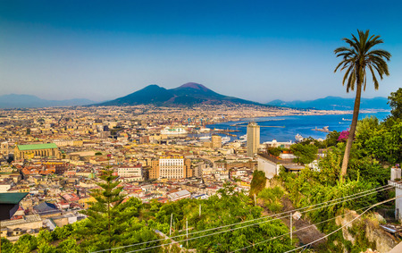 napoli: Scenic picture-postcard view of the city of Napoli with famous Mount Vesuvius in the background in golden evening light at sunset, Campania, Italy