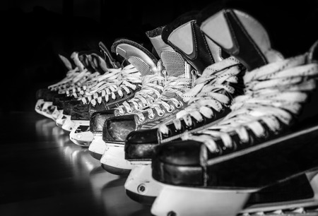 Pairs of hockey skates lined up in a locker room photo