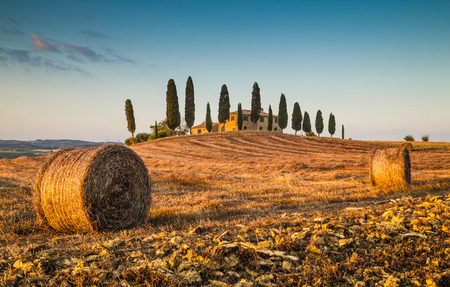 Beautiful Tuscany landscape with traditional farm house and hay bales in golden evening light, Val d Orcia, Italy Stockfoto