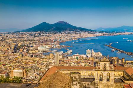Scenic Postkartenblick über die Stadt von Neapel mit dem berühmten Berg Vesuv im Hintergrund in goldenen Abendlicht bei Sonnenuntergang, Kampanien, Italien