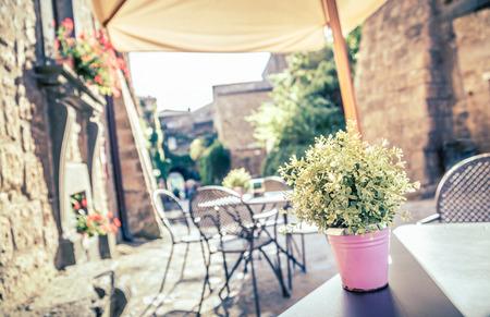 coiffer: Café avec des tables et des chaises dans une vieille rue en Europe avec rétro effet de filtre de style Instagram millésime Banque d'images