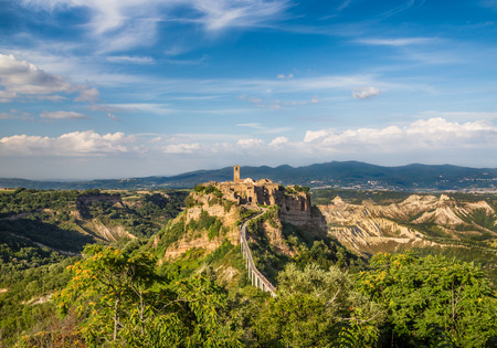 Beautiful view of famous Civita di Bagnoregio with Tiber river valley in golden evening light, Lazio, Italy photo