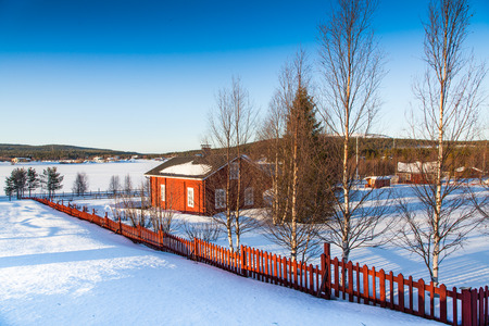 Beautiful winter landscape with house at frozen lake in Scandinavia photo