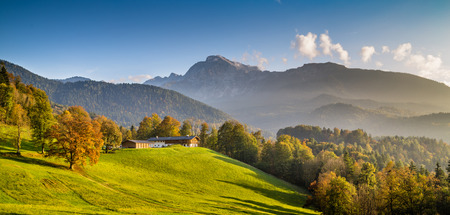 Beautiful autumn landscape with traditional farm house in the Alps in golden evening light