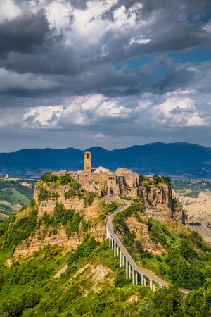 Beautiful view of famous Civita di Bagnoregio with Tiber river valley and dramatic cloudscape at sunset, Lazio, Italy photo