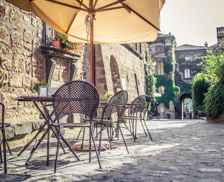 レトロなビンテージ スタイルのフィルター効果を持つヨーロッパの古い通りにテーブルや椅子とカフェ