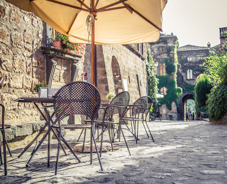 Cafe with tables and chairs in an old street in Europe with retro vintage style filter effect