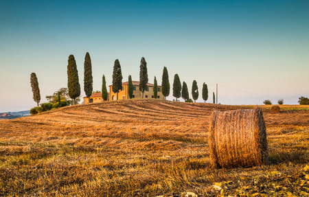 tuscan house: Beautiful Tuscany landscape with traditional farm house and hay bales in golden evening light, Val d Stock Photo