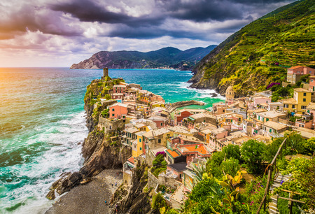 Beautiful view of Vernazza, one of the five famous fisherman villages of Cinque Terre with dramatic cloudscape at sunset in Liguria, Italy photo