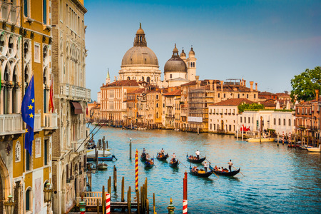 venice canal: Beautiful view of Gondolas on famous Canal Grande with Basilica di Santa Maria della Salute at sunset in Venice, Italy Stock Photo