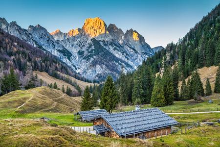 Beau paysage dans les Alpes avec chalets de montagne traditionnels et sommets rougeoyants dans la belle lumière du soir, Nationalpark Berchtesgaden, Bavière, Allemagne