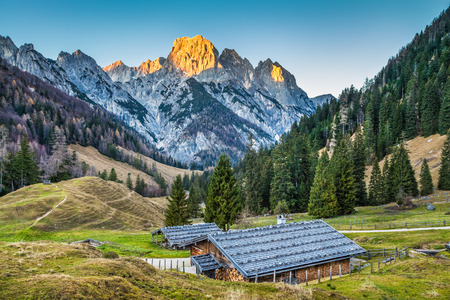 mountains and sky: Beautiful landscape in the Alps with traditional mountain chalets and glowing summits in beautiful evening light, Nationalpark Berchtesgadener Land, Bavaria, Germany