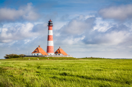 schleswig holstein: Beautiful view of landscape with small pond and lighthouse in the background at North Sea in Nordfriesland, Schleswig-Holstein, Germany Stock Photo
