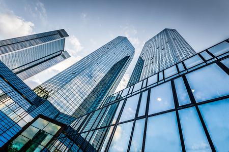 Vue de dessous de gratte-ciel modernes dans le quartier d'affaires contre le ciel bleu