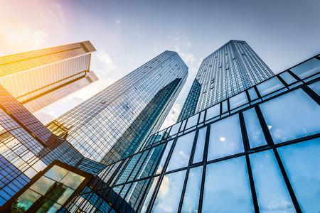 レンズフレア フィルター効果が夕日にビジネス地区モダンな高層ビルの底面図