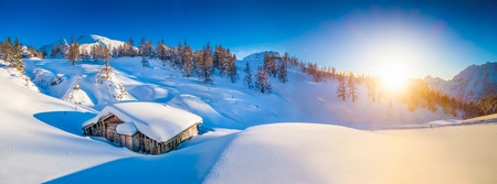 Panoramic view of beautiful winter mountain landscape with snow capped mountain cabin in the Alps in golden evening light at sunset Stock Photo