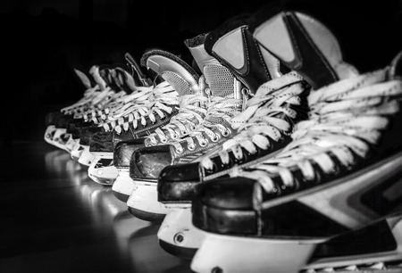 pond: Pairs of hockey skates lined up in a locker room